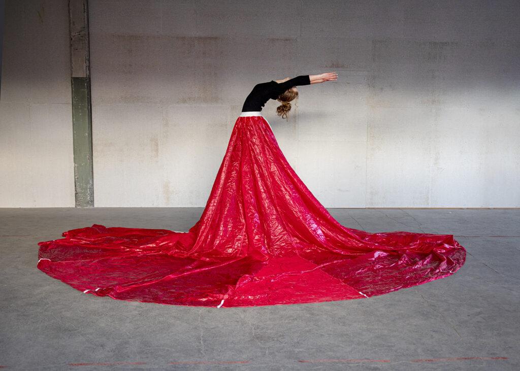 Feuerroter Fallschirm als riesen Rock getragen von einer Tänzerin
